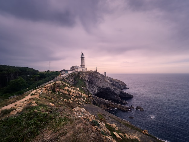 Beautiful winter cloudy sunset, on cliff and lighthouse, of santander, spain Premium Photo