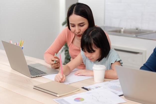 美しい女性と白い紙に描いたり書いたりするかわいいアジアの女の子ハンサムな男はオンラインで働いています。 Premium写真