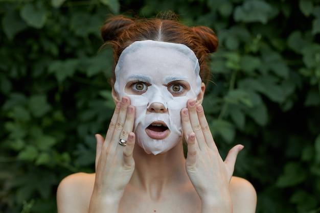 아름다운 여자 노화 방지 마스크 손으로 얼굴을 만져서 놀랐습니다. 프리미엄 사진