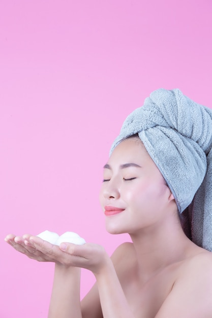 Beautiful woman asia is washing her face on pink background. Free Photo