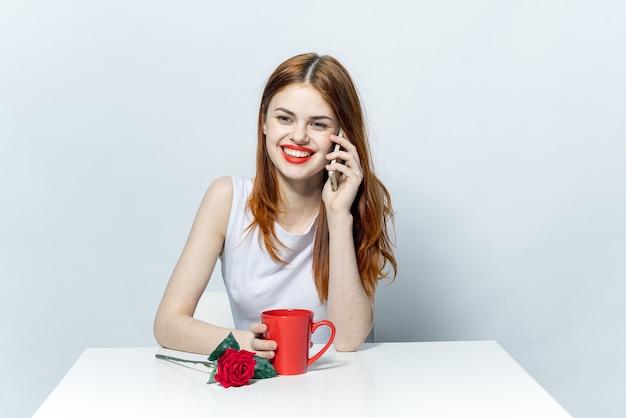 テーブル、明るい背景、感情をポーズで美しい女性 Premium写真