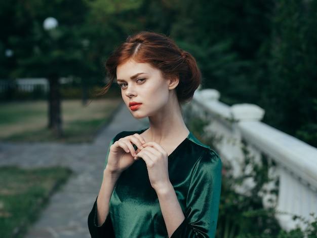 美しい女性の魅力的な外観の化粧品の緑のドレスの豪華な自然。 Premium写真