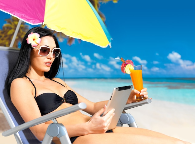 Bella donna sulla spiaggia con ipad. Foto Gratuite
