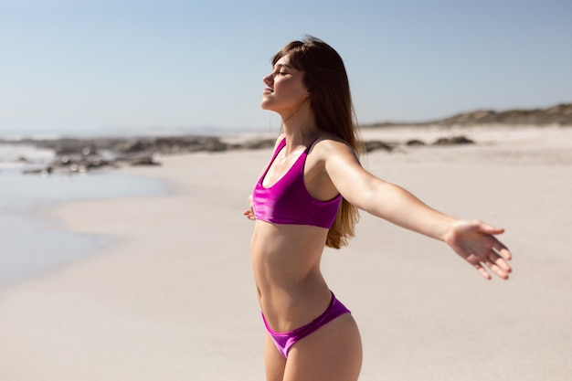 Beautiful woman in bikini with arms stretched out standing on beach in the sunshine Free Photo