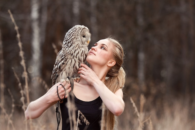 Beautiful woman in a black dress with an owl on his arm. Premium Photo