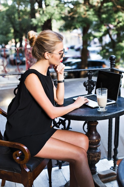 Beautiful woman in black short dress is working at table with laptop on terrace in cafeteria. she looks busy. Free Photo