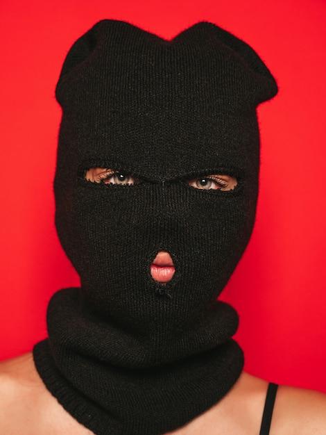 Beautiful woman in black swimwear bathing suit. model wearing bandit balaclava mask. Free Photo