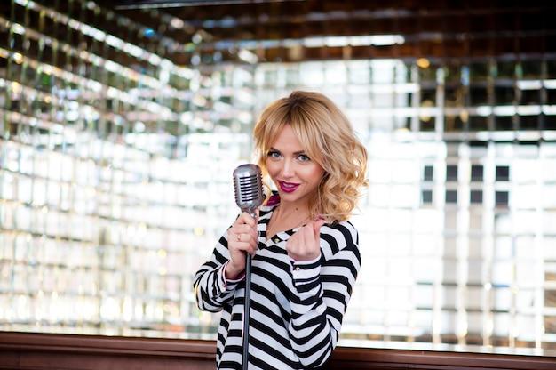 Beautiful woman, blonde, microphone. singing, beautiful smile Premium Photo