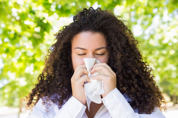 Beautiful woman blowing nose in park Free Photo
