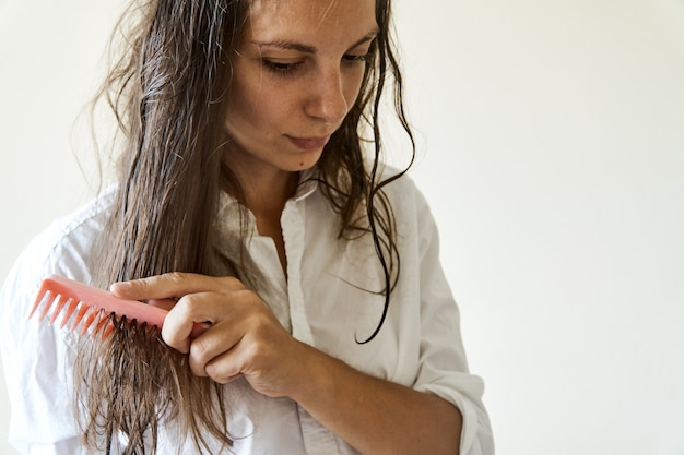 Beautiful woman brushing her wet messy hair after bath with comb. thin hair porblem Premium Photo