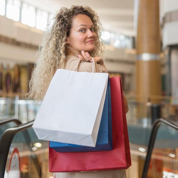モールで買い物袋を運ぶ美しい女性 無料写真
