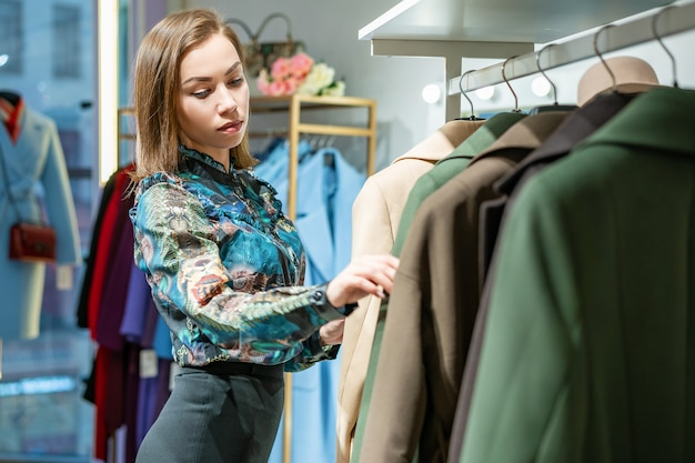 A beautiful woman chooses a coat in the store Premium Photo