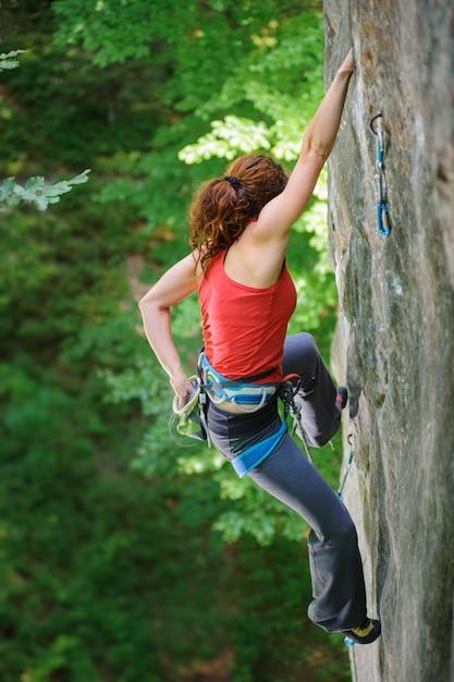Beautiful woman climber climbing steep rock with rope Premium Photo