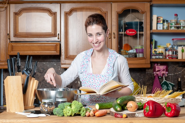 Beautiful woman cooking vegetables with cookbook Premium Photo