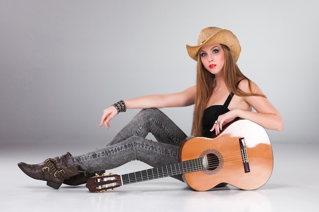 The beautiful woman in a cowboy's hat and acoustic guitar. Free Photo