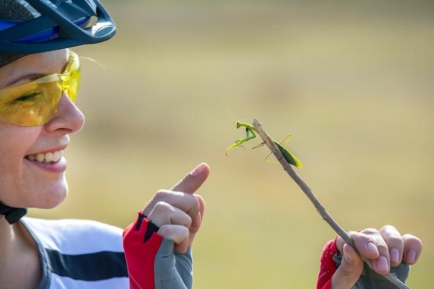 Велосипедист красивая женщина держит жука-богомола. природа и человек Premium Фотографии