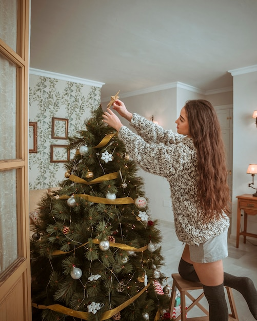 Beautiful woman decorating christmas treein living room Free Photo