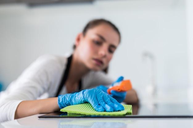 Красивая женщина, работа по дому во время уборки на кухне Бесплатные Фотографии