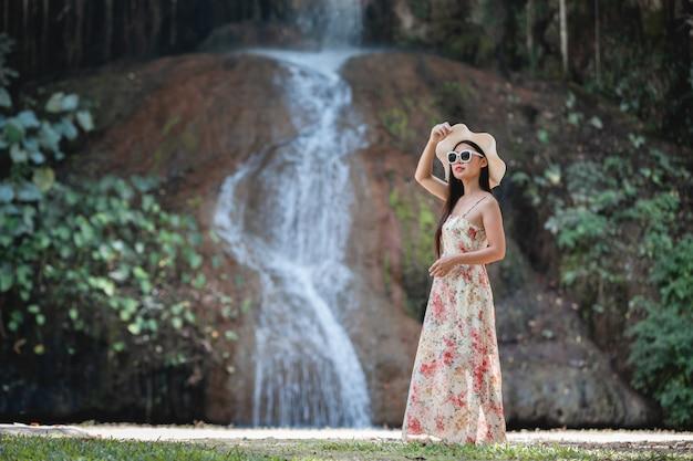 Beautiful woman in dress by the waterfall Free Photo