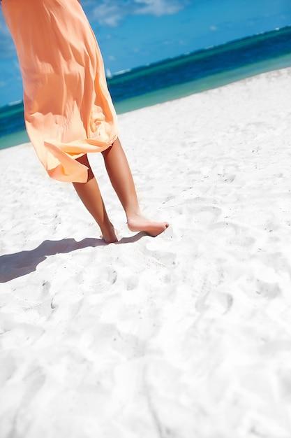 Beautiful woman in dress walking near beach ocean on summer day on white sand Free Photo
