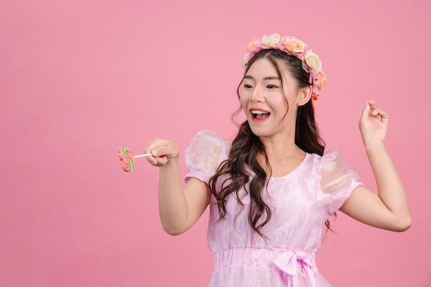 A beautiful woman dressed in a pink princess is playing with her sweet candy on a pink . Free Photo