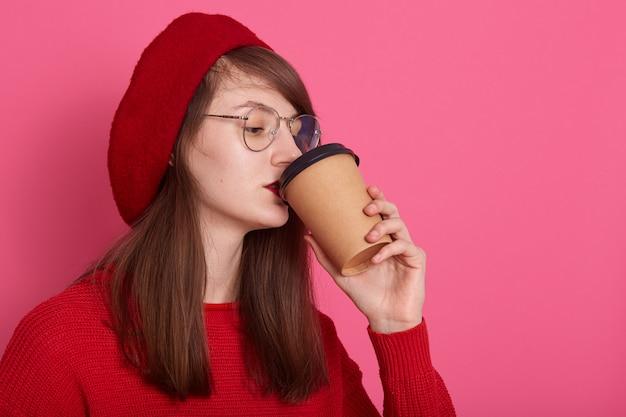 美しい女性は赤いシャツ、眼鏡、ベレー帽、プラスチック製のマグカップでコーヒーのカップを保持している魅力的な女の子のプロフィールを飲んでホットbaverage Premium写真
