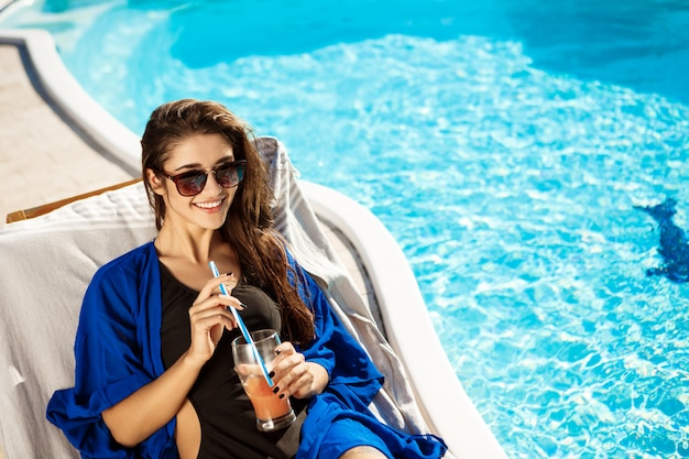 Beautiful woman drinking cocktail, lying on chaise near swimming pool Free Photo