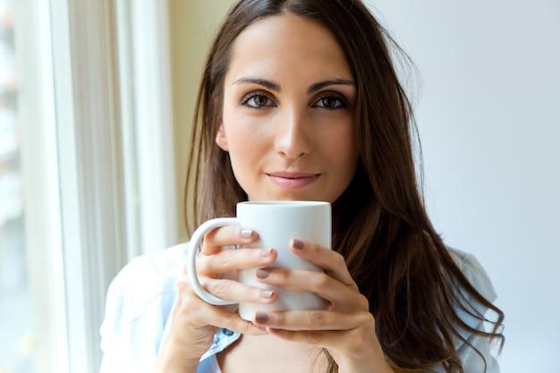 Beautiful woman drinking coffee in the morning near the window. Free Photo