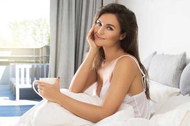 Beautiful woman drinking coffee or tea in bedroom Premium Photo