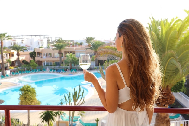 Beautiful woman drinking white wine on outdoor resort terrace Premium Photo