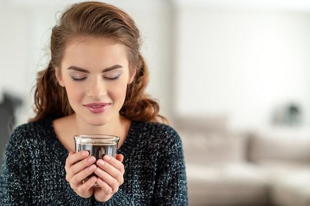 아름 다운 여자는 커피를 마시고 맛을 즐기고 있습니다. 차 한잔과 함께 편안한 꽤 젊은 성인 소녀. 무료 사진