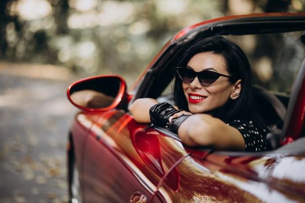 Красивая женщина за рулем красного кабриолета Бесплатные Фотографии