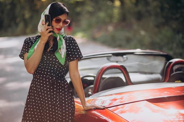 赤いカブリオを運転する美しい女性 無料写真