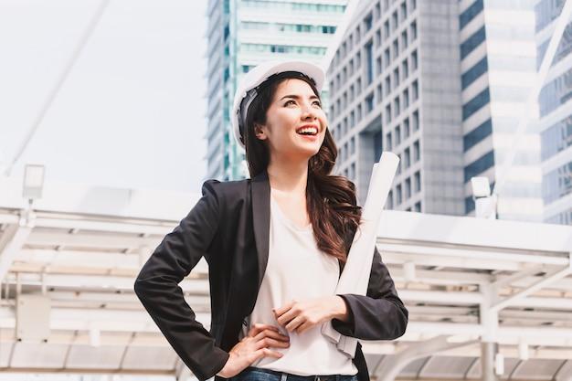 Beautiful woman engineer holding blueprint on city background Premium Photo