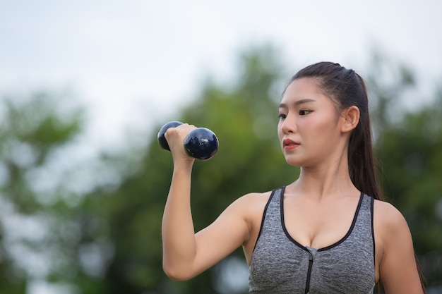 Beautiful woman exercising upper arm by lifting dumbbells on the park. Free Photo