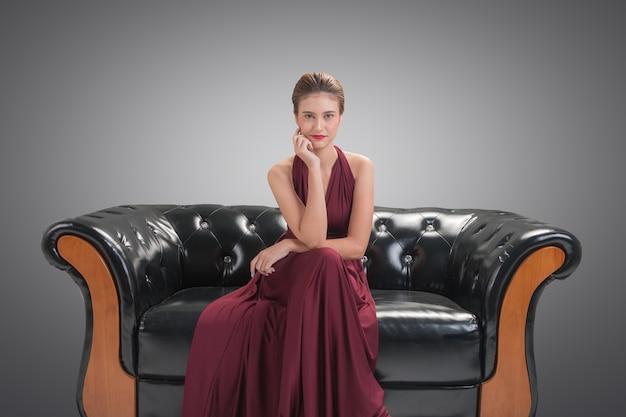 Красивая женщина модель модель сидит и позирует на диване Premium Фотографии