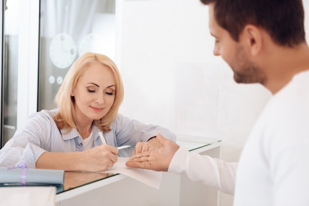 Beautiful woman fills out form for obtaining certificate Premium Photo