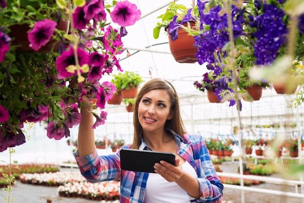 園芸用品センター温室チェック花販売でタブレットコンピューターを使用して美しい女性花屋 無料写真