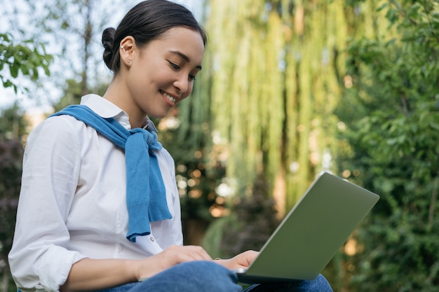 Beautiful woman freelancer using laptop, working, typing, searching information, sitting in park Premium Photo