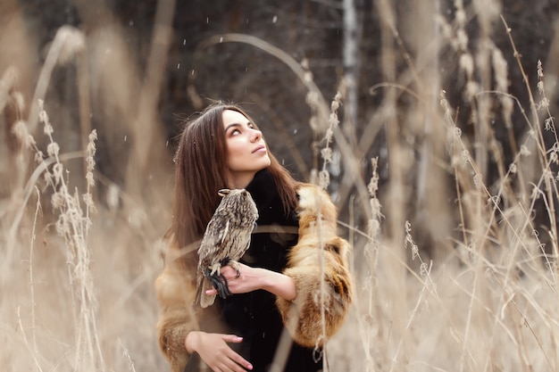 Beautiful woman in a fur coat with an owl on hand Premium Photo