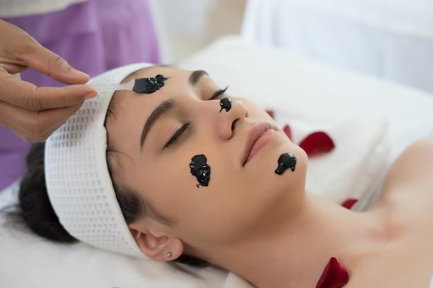 Beautiful woman getting facial black mud mask at beauty salon. Free Photo