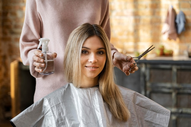 Beautiful woman getting her hair cut at home by hairdresser Free Photo