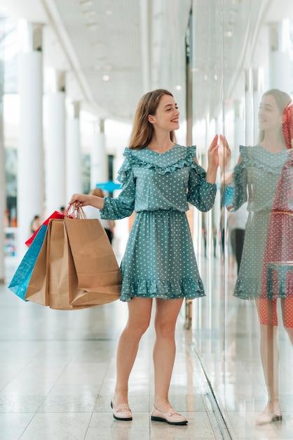 Beautiful woman going window shopping Free Photo