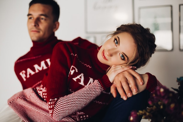 Beautiful woman and handsome boyfriend posing in red sweaterss Premium Photo