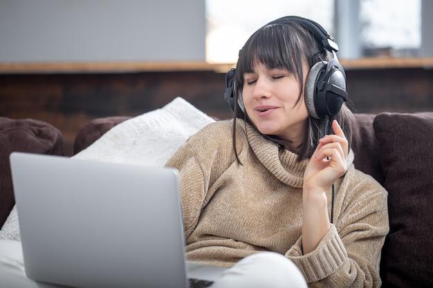 Bella donna in cuffie che ascolta la musica a casa sul divano con un computer portatile. Foto Gratuite