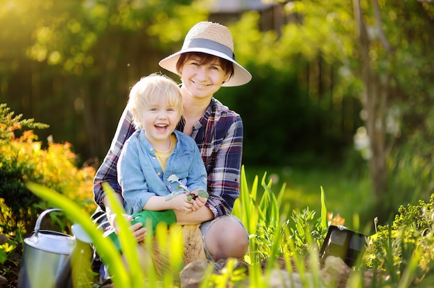 Beautiful woman and her cute son planting seedlings in bed in the domestic garden at summer day Premium Photo