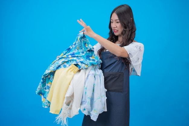 Beautiful woman holding a basket of clothes on blue Free Photo