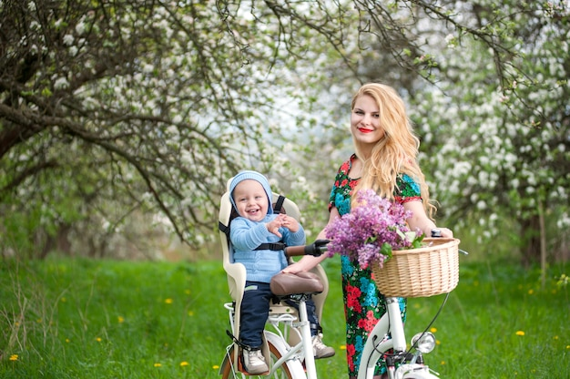 Beautiful woman holding bike and happy baby sitting in bicycle chair in the basket lay a bouquet of lilacs Premium Photo