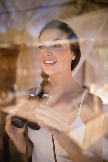 Beautiful woman holding binoculars Free Photo