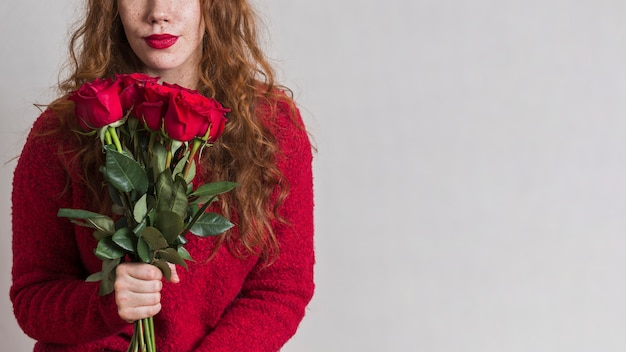 Beautiful woman holding a bouquet of roses Free Photo